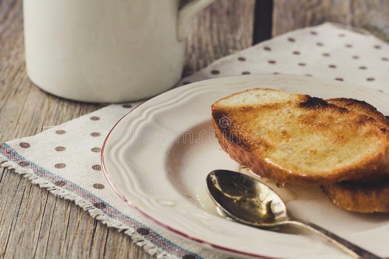 Pains grillés avec du miel du plat blanc photos libres de droits