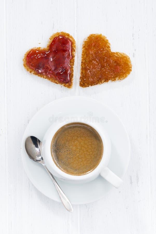 Pains grillés dans la forme de coeur avec de la confiture de fruit et la tasse de café images libres de droits