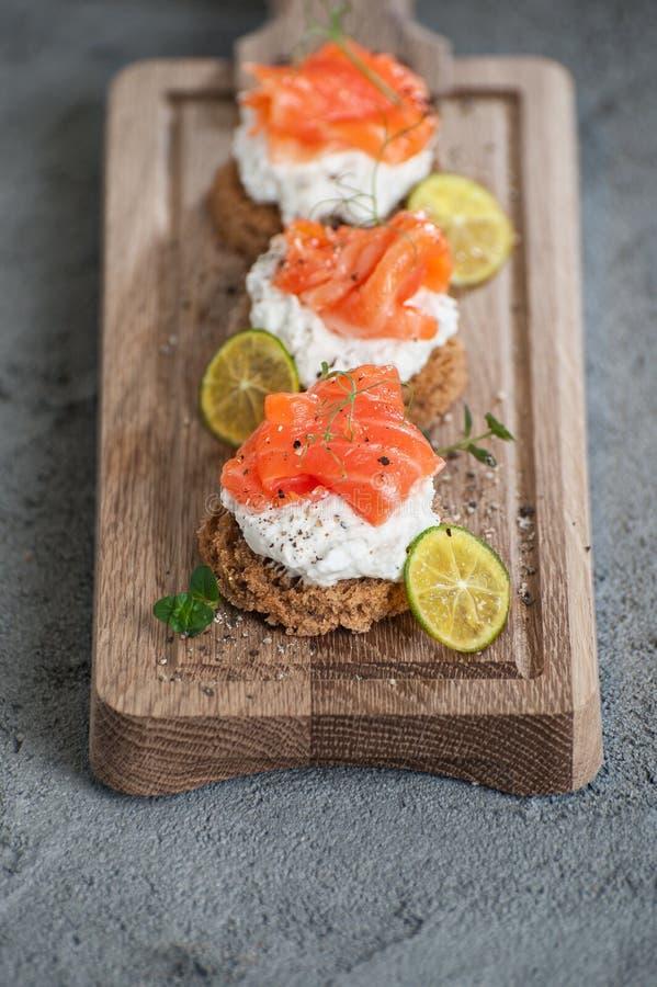 Pains grillés miniatures avec le fromage de saumon et blanc légèrement salé c photos stock