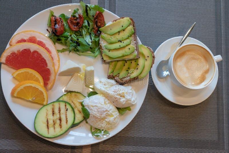 Pains grillés sains délicieux de petit déjeuner avec l'avacado, tomates sèches, fromage, apelsin, pamplemousse, oeuf poché, courg photographie stock libre de droits