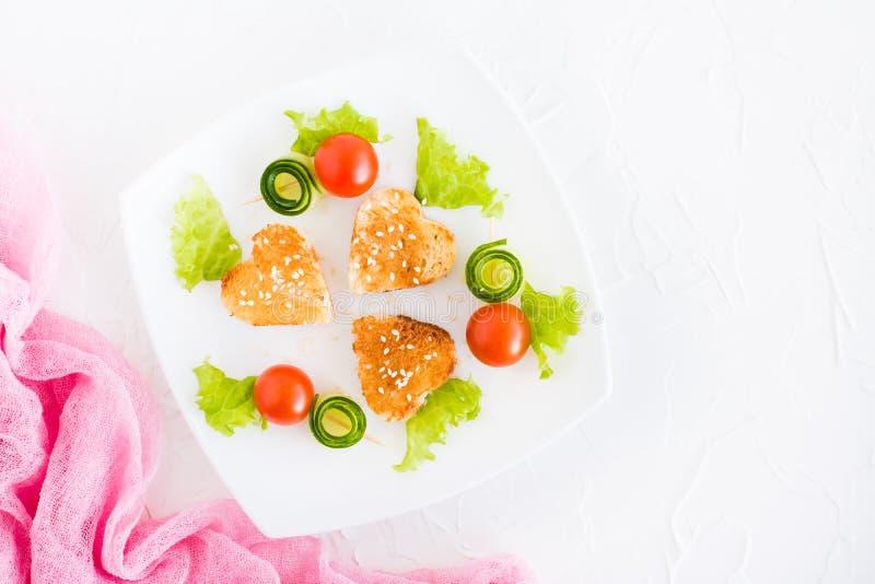 Pains grillés sous forme de coeur, de cerise et de concombre d'un plat photo libre de droits