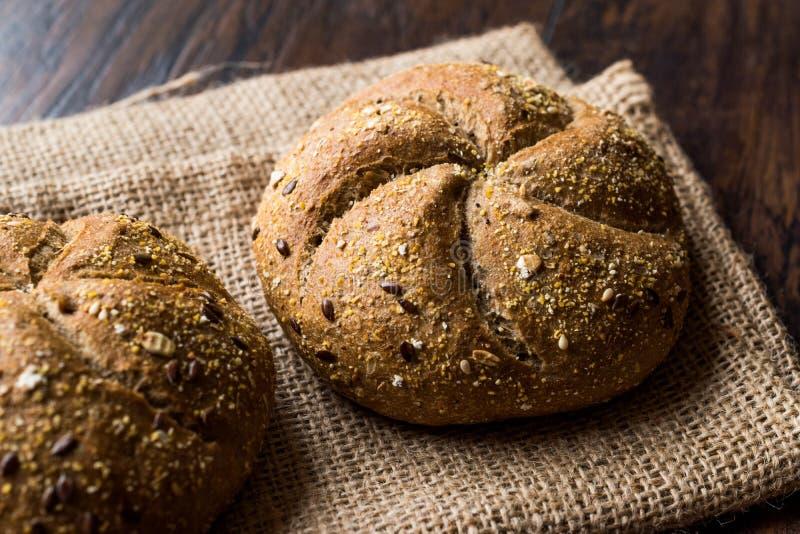 Pains ronds fraîchement cuits au four de petit pain de Kaiser de grain de blé entier avec le sac photographie stock