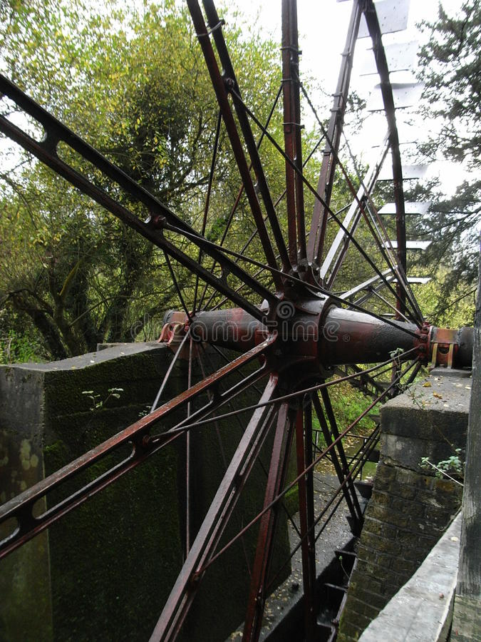 Painshill Metal water wheel, very large from England. Industrial Revolution bravura 1830, restored, cycle type wheel, spokes and paddles, on plinth stock photo