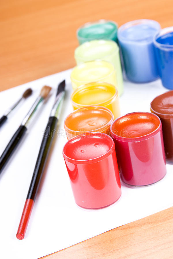 Paint. Colorful paint with paintbrush on table stock photography