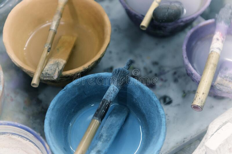 Paint in bowls with simple brushes in an artist studio stock images