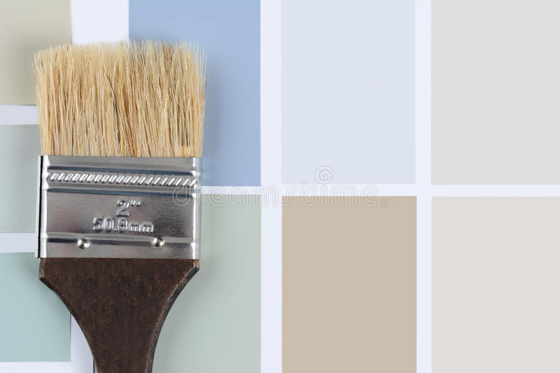 Paint Brush Brown Handle on Color Chips. Overhead shot of a paint brush with a brown handle laying on a sheet of color samples. Horizontal format with copy space royalty free stock image