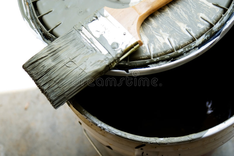 Paint Brush and Bucket. A paint brush on top of a bucket, a very popular shade of green for homes royalty free stock photos