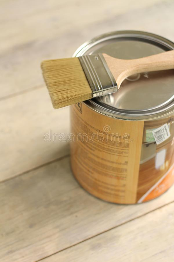 A paint brush lies on a metal can on an old white vintage wooden plank table. Place for text or logo. Top, view, renovation, house, home, paintbrush, repair royalty free stock image