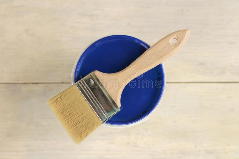 A paint brush is lying on the blue lid of a plastic paint bucket on an old white vintage wooden plank table. Place for text or. Logo, background, cover, liquid royalty free stock images