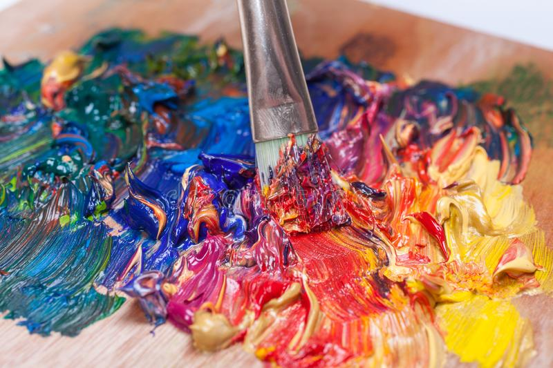Paint brush mixed different color oil paints. colorful acrylic. modern art concept stock photo