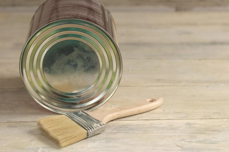 A paint brush is next to a metal can on an old white vintage wooden plank table. Place for text or logo. Top, view, renovation, house, home, paintbrush, repair royalty free stock images