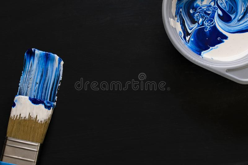 Paint brush painting with blue color. in the upper corner is a plate with mixed white and blue colors. close-up. dark background. royalty free stock photo