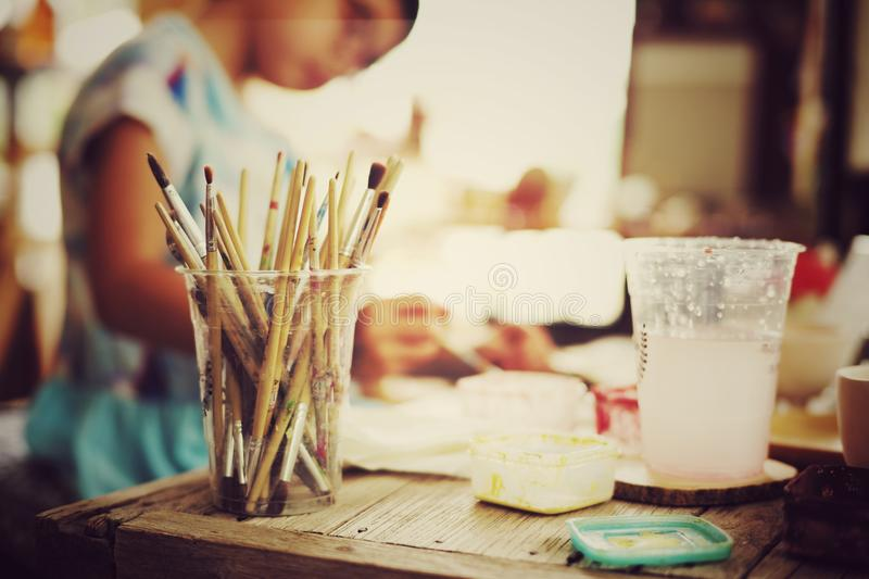 Paint brush in the plastic glass. At the art workshop class for kids royalty free stock images