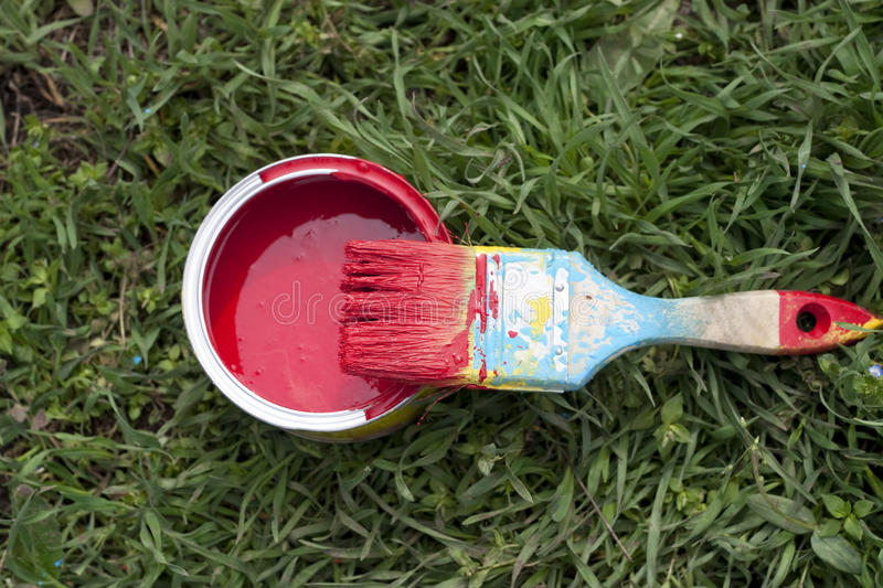 Paint brush and pot of red paint stock image