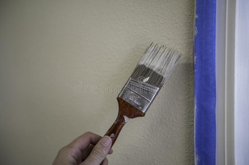Paint Brush Trim. Painting with a paintbrush while avoiding the trim royalty free stock images