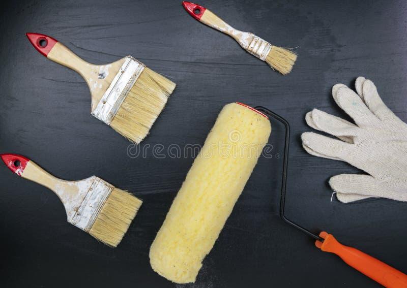 Paint brush and white glove on black background. stock photo