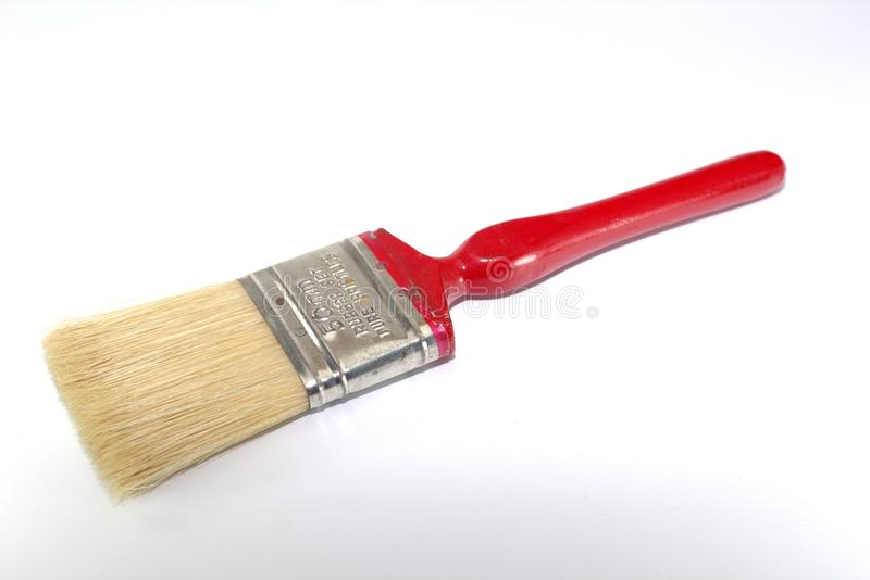Paint brush width 2 inches with a red handle on a white background. Close-up stock image