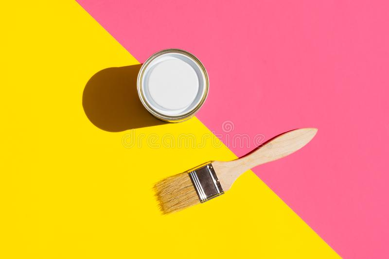 Paint brush with wooden handle can of varnish on trendy duotone pink yellow background. Interior design home refurbishing fashion. Concept. Modern pop art style royalty free stock photography