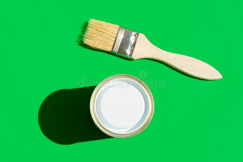 Paint brush with wooden handle can of varnish on trendy green background. Interior design home refurbishing fashion concept. Modern pop art style with harsh royalty free stock photos