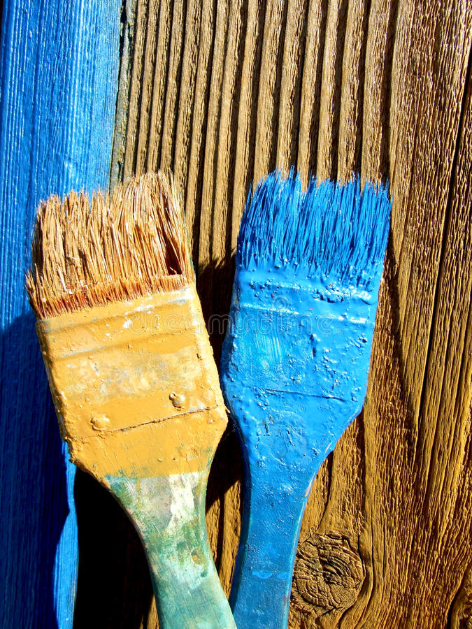 Paint brushes. Two colored paint brushes on wood surface royalty free stock photography
