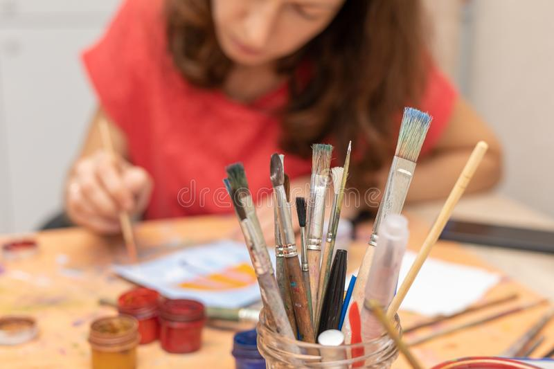 Paint brushes on blur background of paint and a girl is engaged in painting. gouache painting stock photos