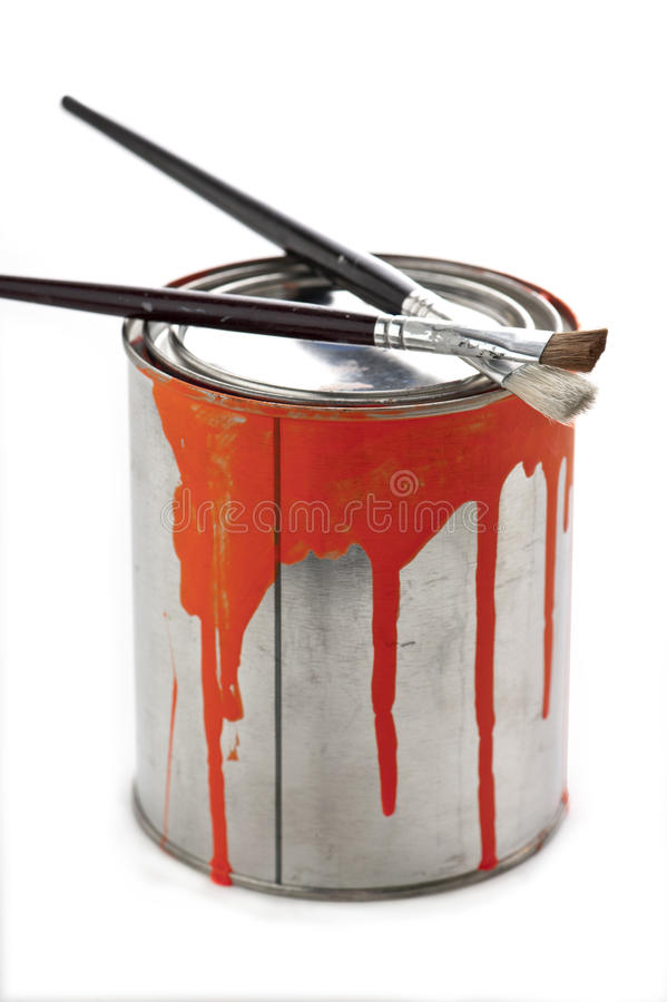 Paint brushes on can. Two artists fine art paintbrushes resting on top of a paint can with orange paint dripping down the side of the can royalty free stock photography