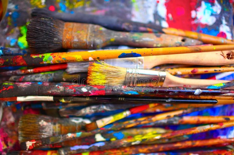 Paint brushes of different sizes, stained by vivid colors, close stock images