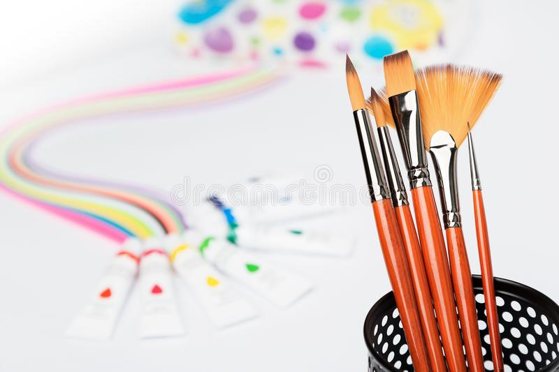 Paint brushes, multicolored paints in tubes, paper rainbow on a white background, tools for drawing stock photo