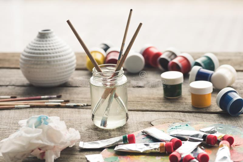 Paint brushes in a solvent and scattered containers with poster paints and acrylic royalty free stock image