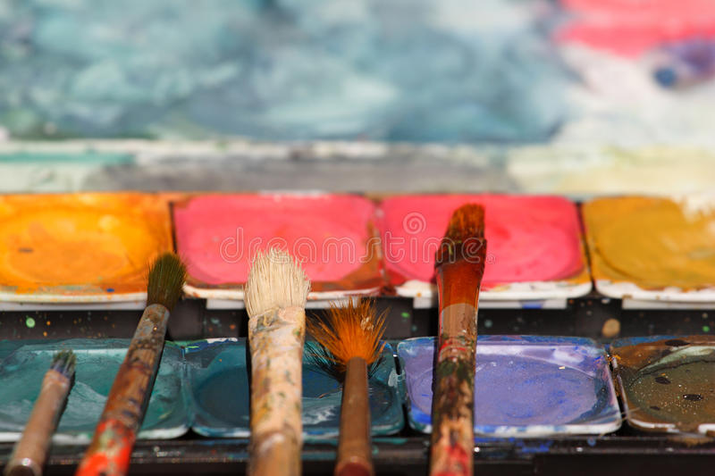 Paint brushes on watercolors royalty free stock photos