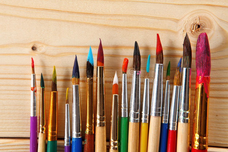 Paint brushes on wooden background. Paint brushes on wooden backdrop royalty free stock images