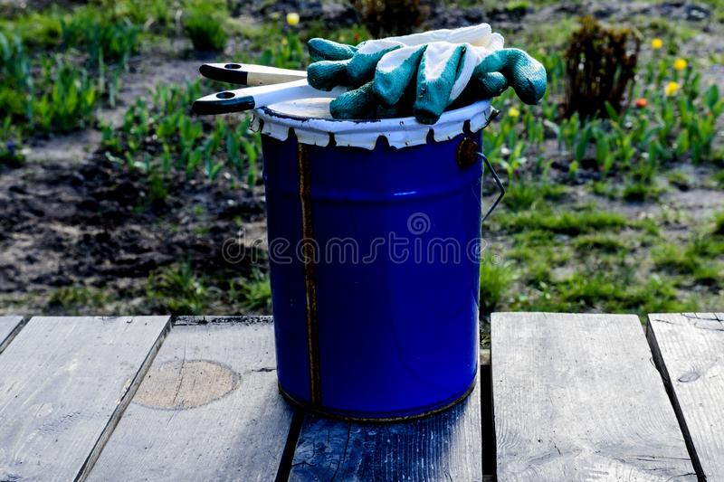 Paint can lying on the terrace of a private house with a brush and gloves, ready to be opened and painted. home repair and mainten. A paint can lying on the royalty free illustration