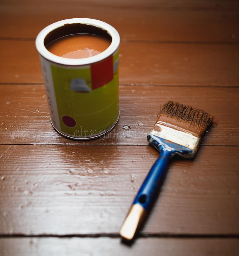 Paint can and paintbrush, floor painting renovation stock images