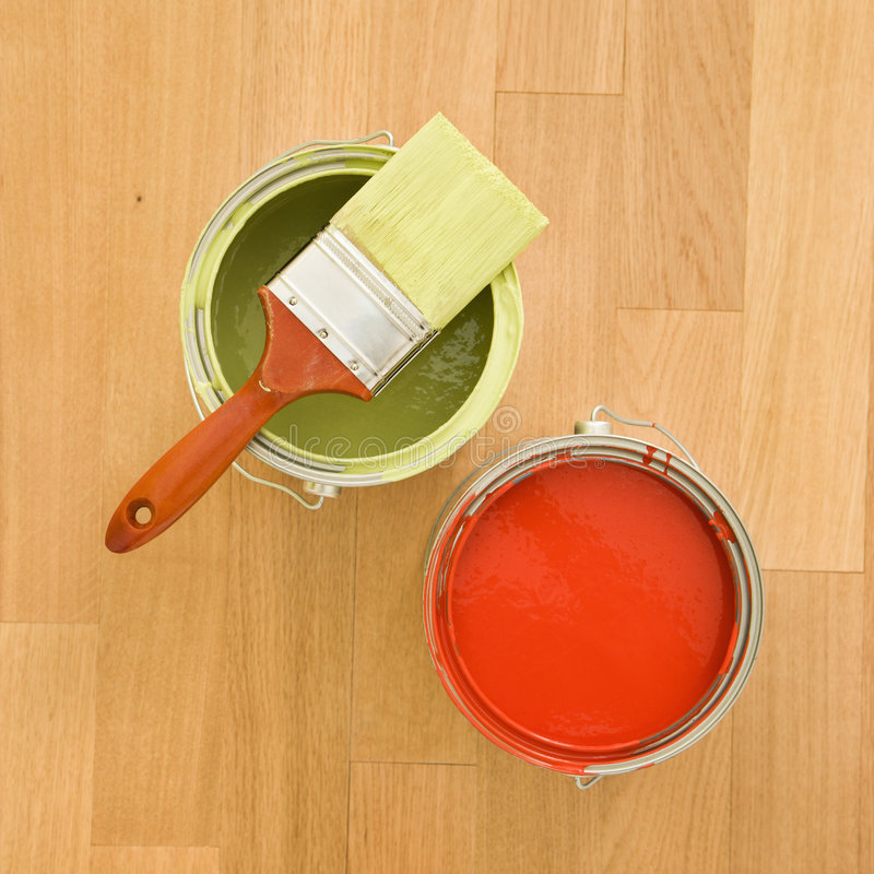 Paint cans and brush. High angle of paintbrush with paint cans on wood floor royalty free stock photo