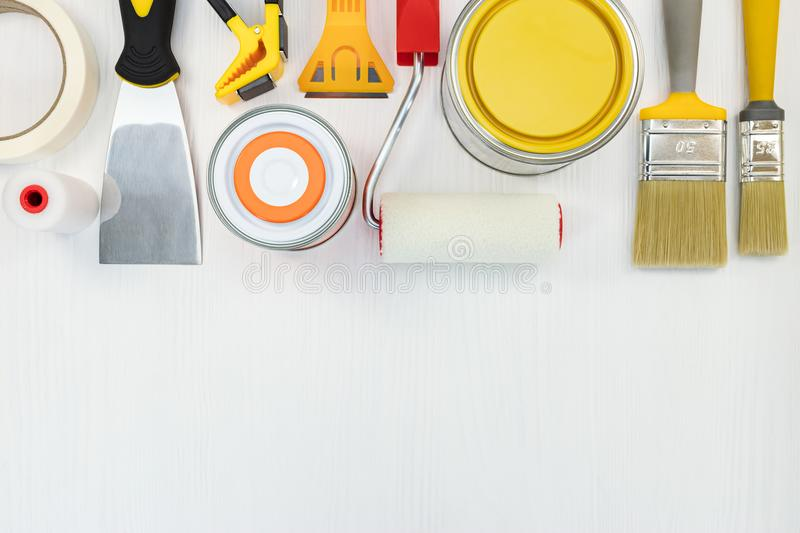 paint cans, brushes, putty knife and rollers on white wooden background stock photo