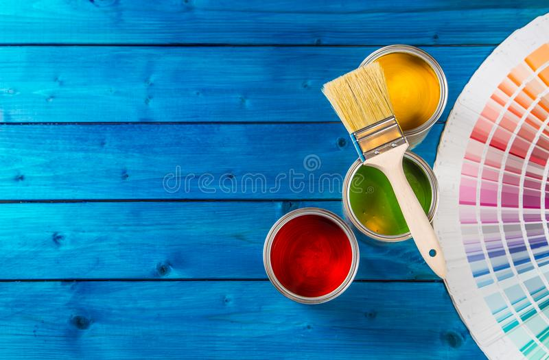 Paint cans color palette, cans opened with brushes on blue table stock photos