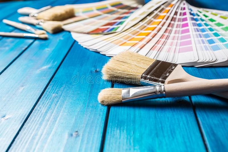 Paint cans color palette, cans opened with brushes on blue table stock images