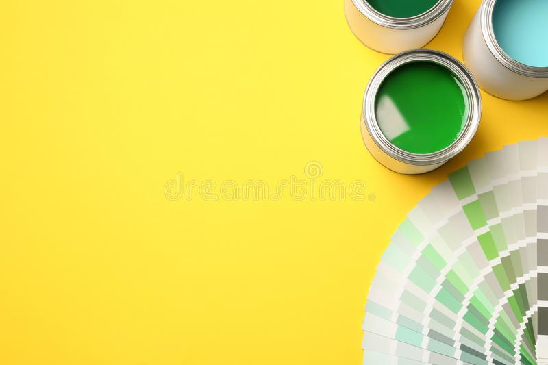 Paint cans and color palette on yellow background, top view. stock photos