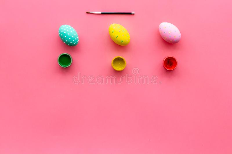 Paint eggs for Easter celebration on pink background top view mock up royalty free stock photo