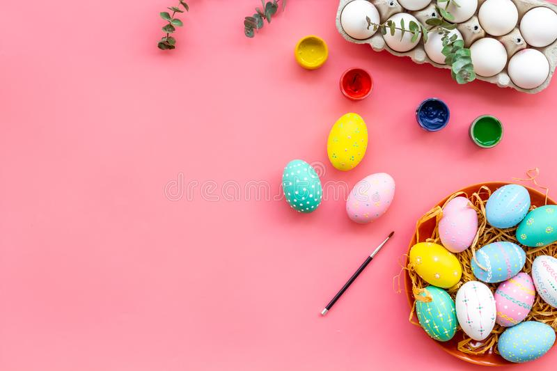 Paint eggs for Easter celebration on pink background top view mock up stock photo