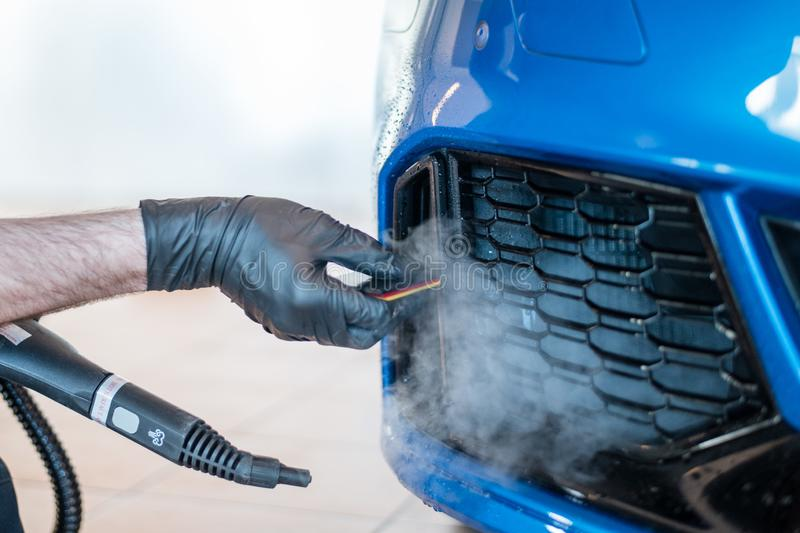 Worker is applying paint protection film with squeegee on car buffer. Paint protection a thermoplastic urethane often self healing film applied to painted stock images