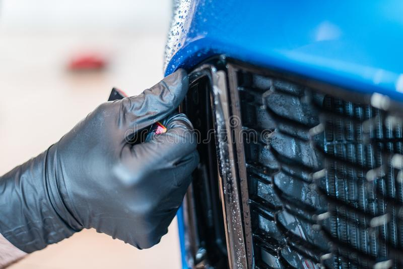 Worker is applying paint protection film with squeegee on car buffer. stock photography