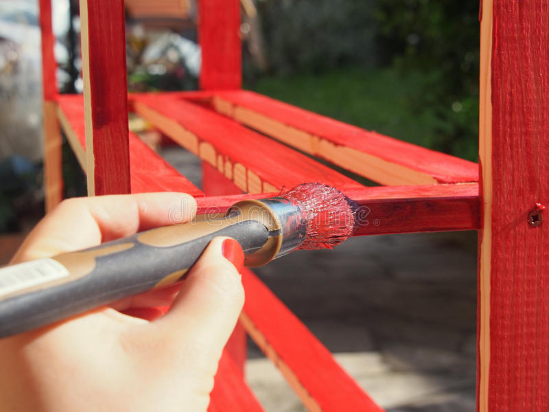 Paint it red. Woman hand with red nail polish painting a pine tree shelf furniture with fresh red paint stock photos