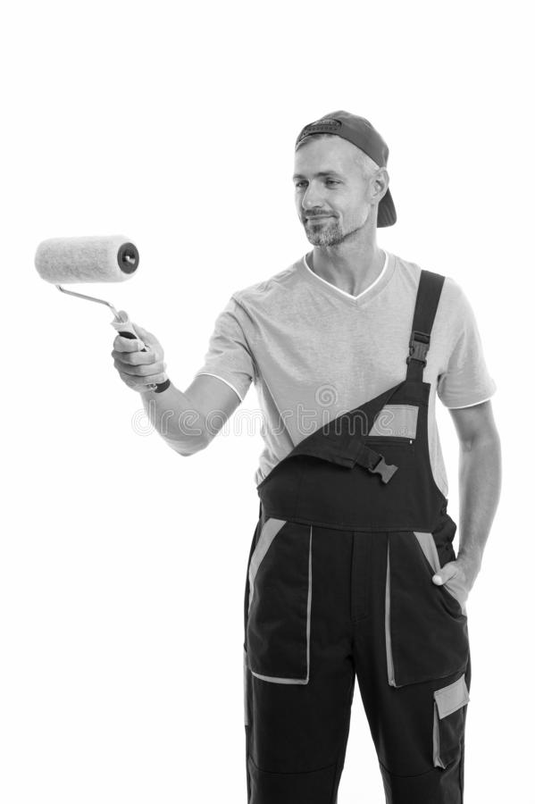Paint and renovate. Decorator painting wall. Man in cap hold paint roller white background. Worker painter decorator royalty free stock image