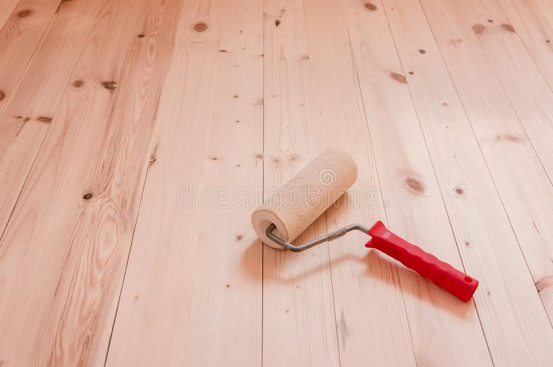 Paint roller brush on wood background royalty free stock photography