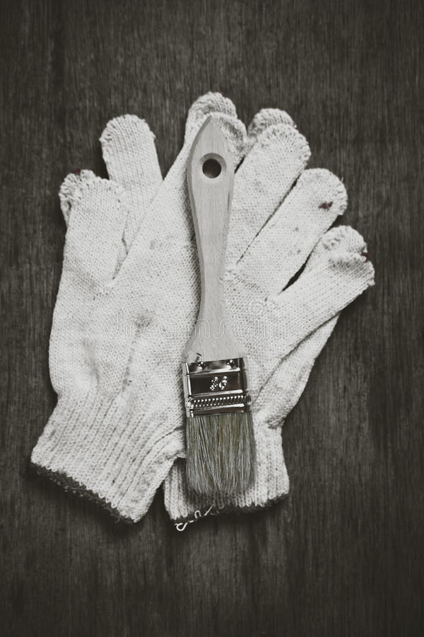 Paint roller brushes working gloves. On wooden board construction concept stock photos