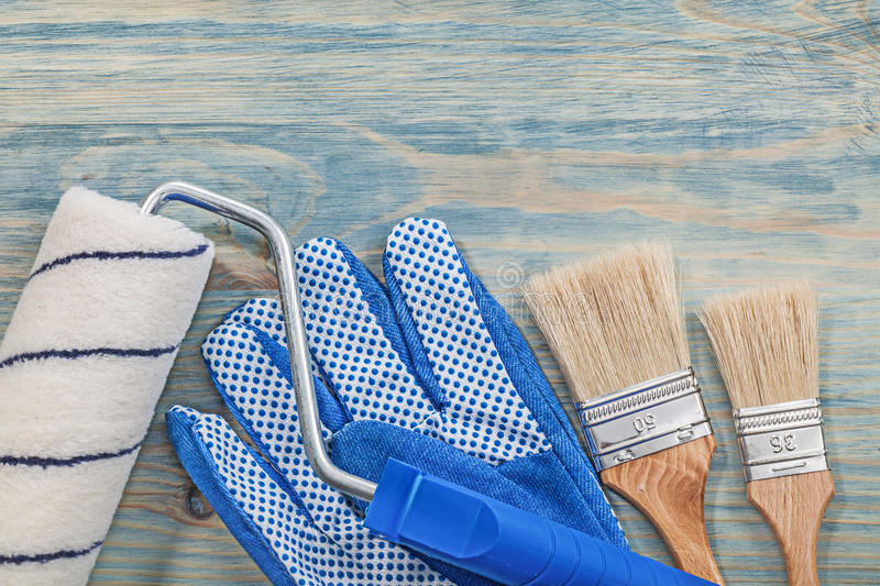 Paint roller brushes working gloves on wooden board horizontal v. Ersion construction concept royalty free stock photo