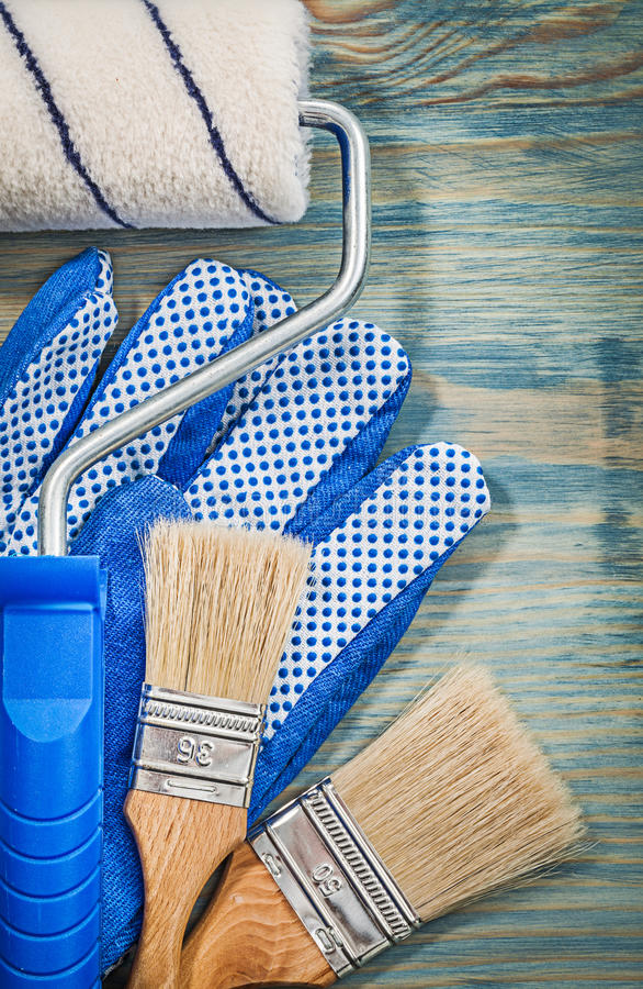 Paint roller brushes working gloves on wooden board top view con. Struction concept stock images