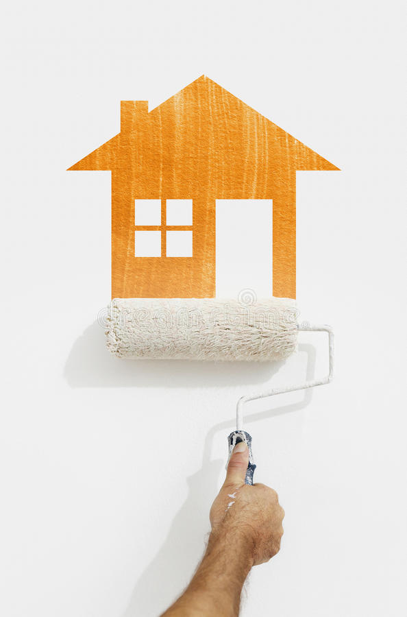 Paint roller hand with orange house symbol painting on wall stock photo