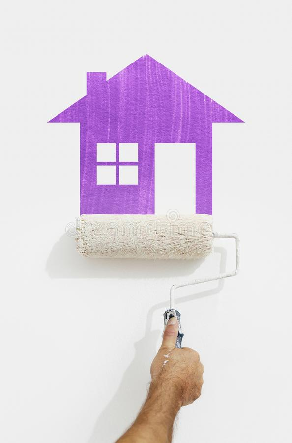 paint roller hand with purple house symbol painting on wall isolated on white stock image